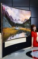 A model leans on the edge of LG 21:9 aspect ratio CURVED ULTRA HD TV model 105UC9 at CES 2014