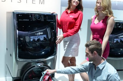 Male and female models posing next to LG TWINWash™ washing machine. A male putting a small laundry into the Mini washer.