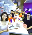 """A group of people from all around the world sit around a table behind a model holding up a """"LG G4 Consumer Experience Campaign"""" sign."""