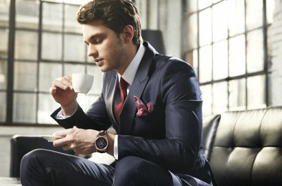 A business man in a suit wears LG's Watch Urban while drinking coffee on a couch.