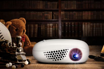 Front view of LG MiniBeam Nano sitting on desk in a dark room