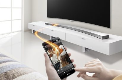 Front view of the LG Curved Sound Bar with a model controlling it via the Soundbar Smartphone App Controller