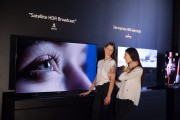 Two visitors experience satellite HDR content utilizing ASTRA'S system on an LG TV at LG's IFA 2015 booth