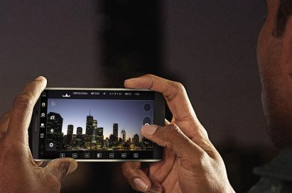A man takes a photo of a city skyline at night with the LG V10