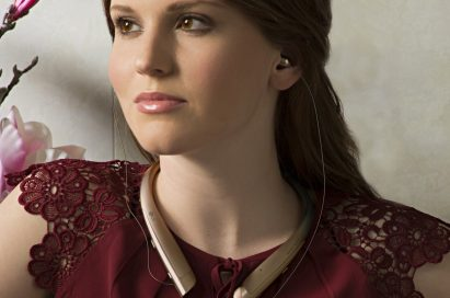 A woman with the LG TONE Platinum™ in Gold around her neck and the retractable ear buds in her ears