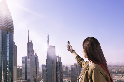 A woman is taking a picture of the skyscrapers in Dubai, United Arab Emirates, with the LG 360 CAM