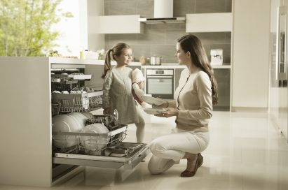 Mother and daughter taking out dishes from LG dishwasher