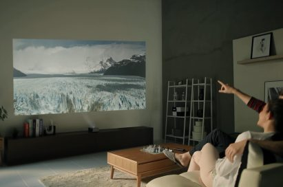 A couple sitting on a couch watching a scene of the Antarctic with the LG Minibeam projector