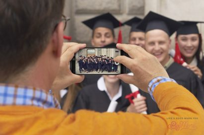 A man taking a photo of a group of graduates with the LG V20's Wide Angle camera