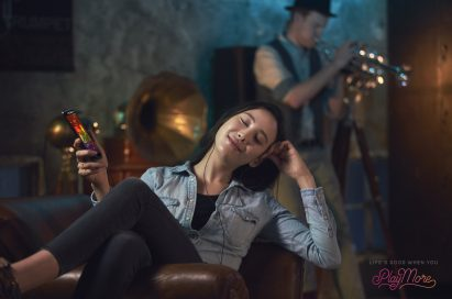 A woman reclining in a chair listening to music via headphones with the LG V20's Hi-Fi Quad DAC