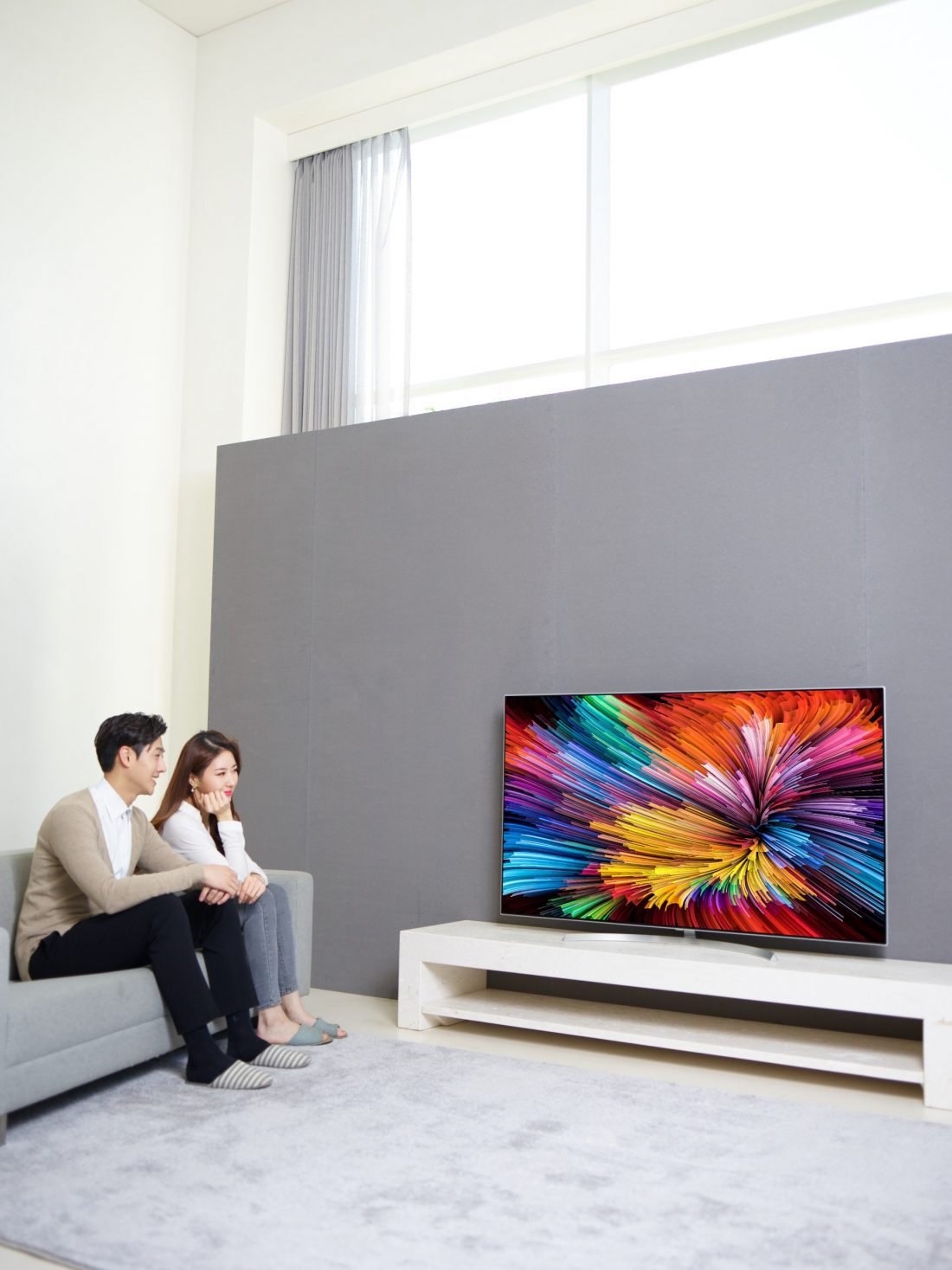 Another view of a couple sitting on a couch watching the LG SUPER UHD TV (model SJ95)