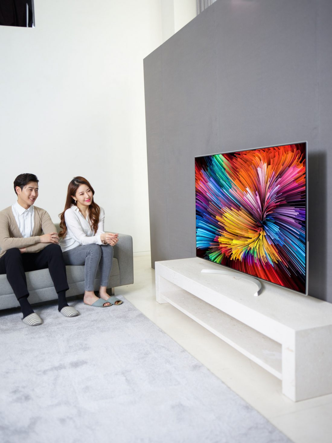 Another different shot of a couple sitting on a couch watching the LG SUPER UHD TV (model SJ95)