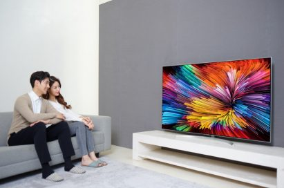 A couple sit on a couch while watching colorful images on the LG SUPER UHD TV