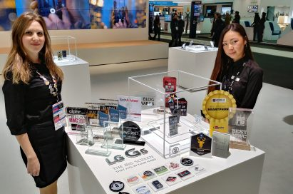 Two LG promoters standing behind two LG G6 devices and 31 booth awards that were given to the LG G6 at MWC 2017