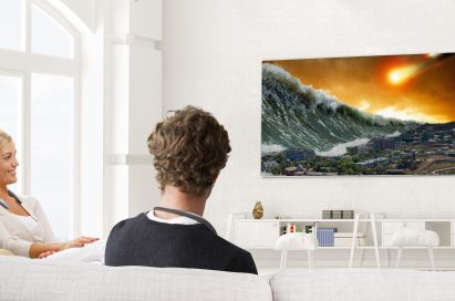 A man and woman are watching television with the LG Tone Studio around both of their necks