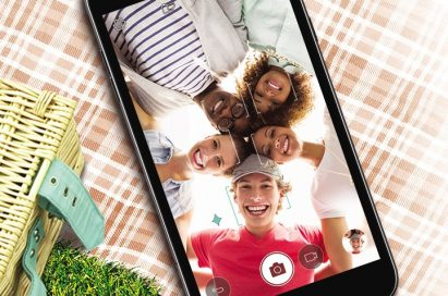The LG Xpower2 lying on top of a picnic blanket, with a group of people captured in the camera frame while taking a selfie