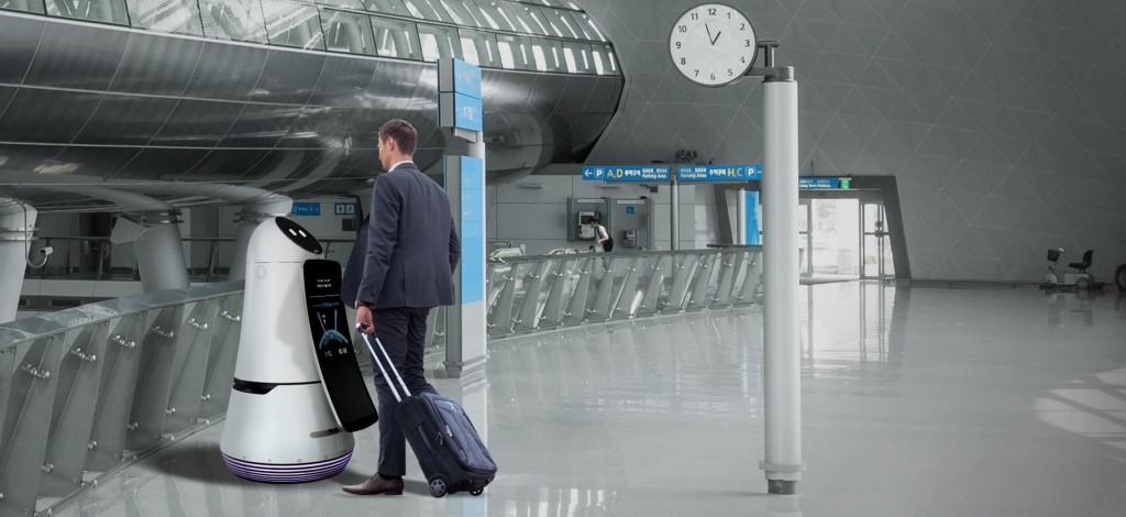 A man checking in at the airport with the help of the LG Airport Guide Robot.
