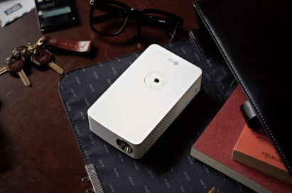LG MiniBeam Projector model PH30J with scattered objects including a calculator, pair of glasses and keys
