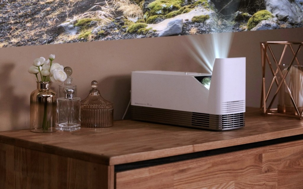 The LG ProBeam Projector model HF85J placed on top of living room furniture.