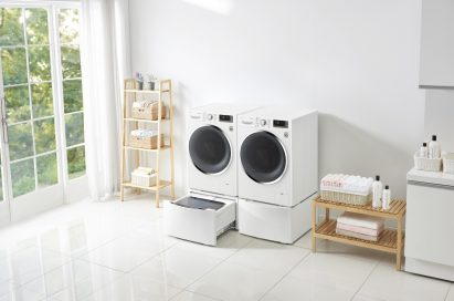Side view of one LG washing machine with the TWINWash™ Mini unit open next to LG dryer with the pedestal unit closed in a laundry room