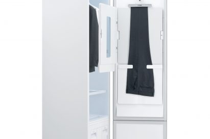 Side view of LG Styler with the door open, showing trousers hanging on the door and a jacket and white shirt hanging inside