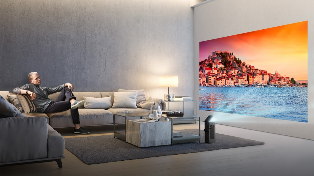 A man seated on a couch watches video projected onto a wall from LG's HU80K series 4K UHD projector.