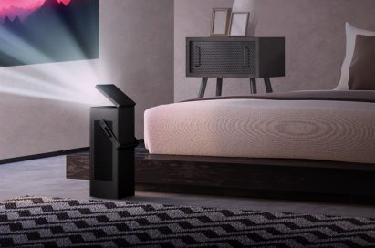 An LG 4K UHD projector set up in a bedroom projects video onto a wall from a short distance
