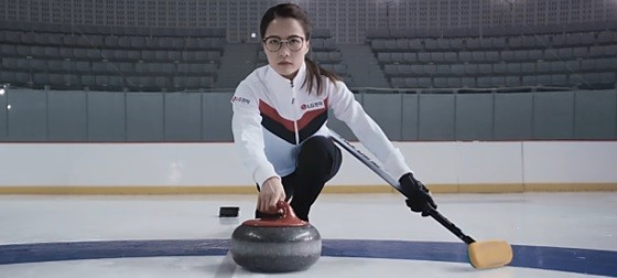 Skip Kim Eun-jung launches a stone with a broom in her left hand.