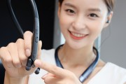 A woman with the LG TONE Platinum SE in Black around her neck pointing at the Google Assistant button on the LG TONE Platinum SE in her hands