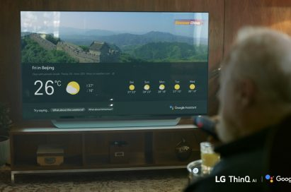A man using Google Assistant on an LG TV with a remote control to check the weather