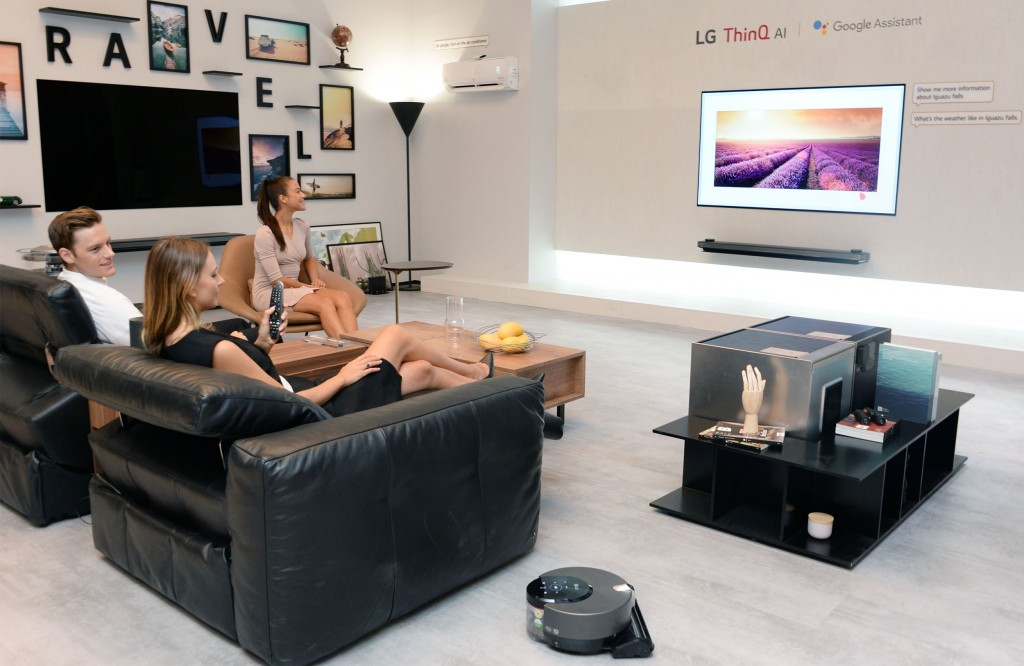 Models pose with LG ThinQ AI TV at the LG booth at IFA 2018.