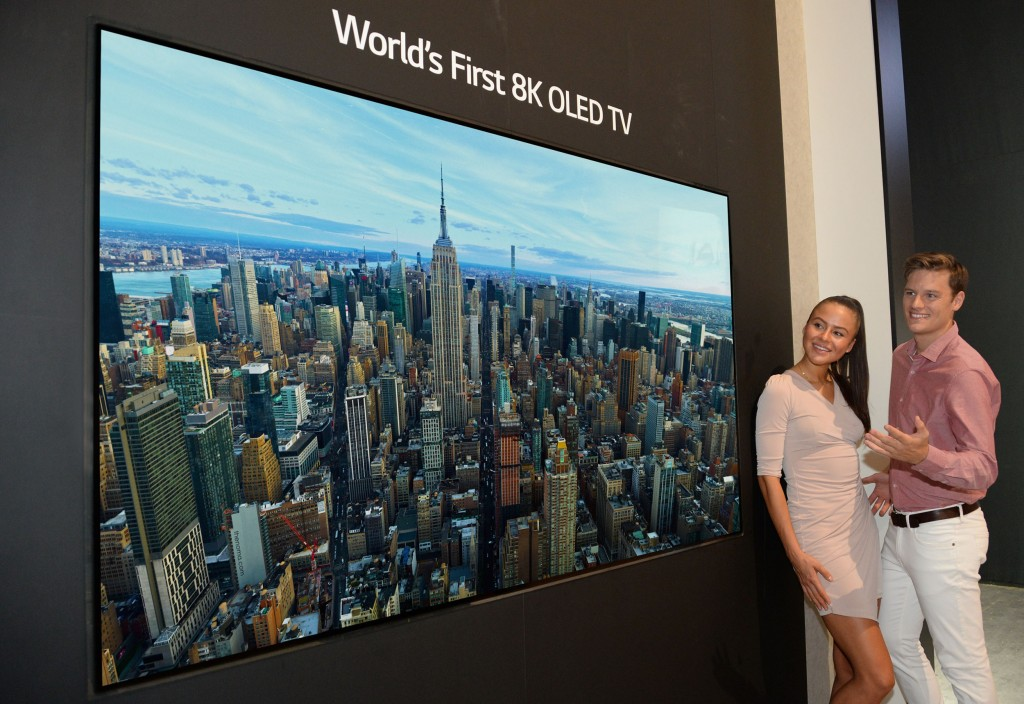 Two models look in awe at the world's first LG 8K OLED TV displayed at IFA 2018.