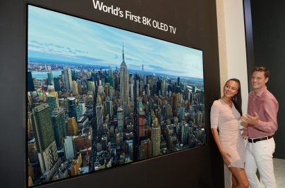 Two models look in awe at the world's first LG 8K OLED TV displayed at IFA 2018