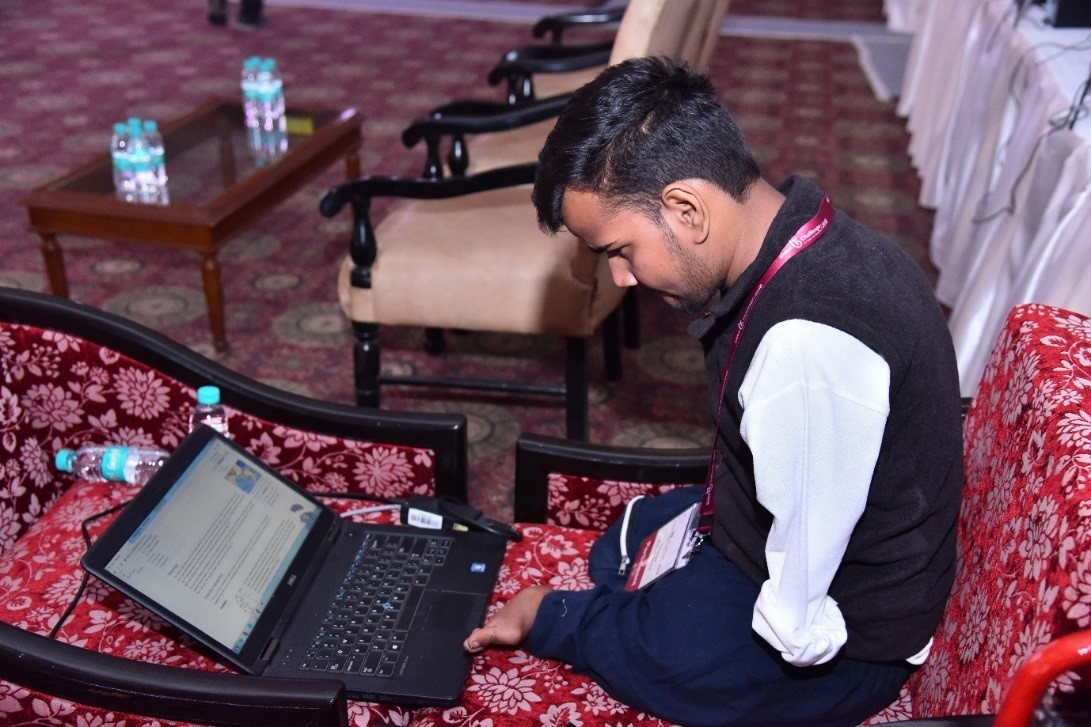 A participant looks down at his laptop computer