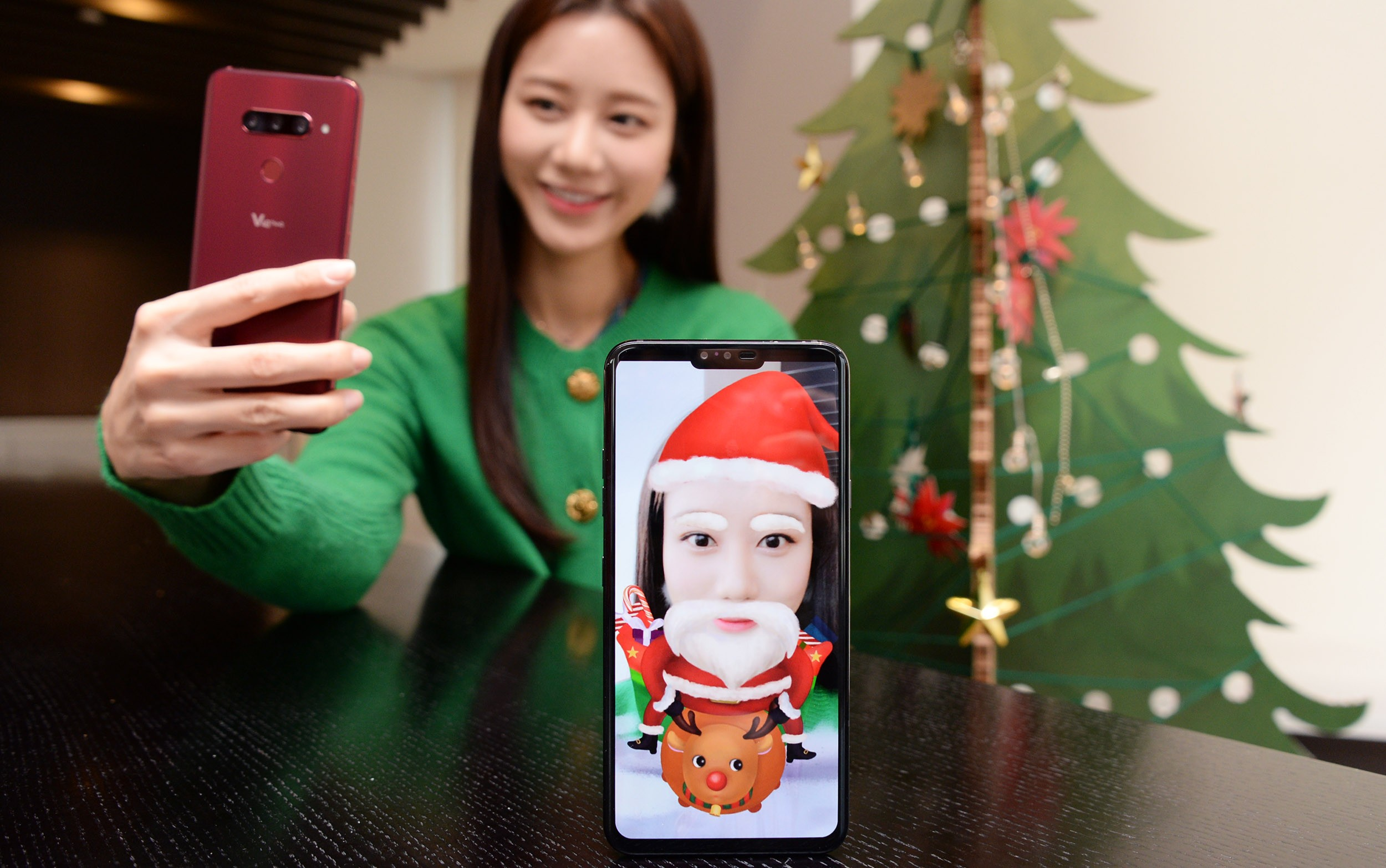 A woman turns her selfie into a Santa Claus lookalike by using the Augmented Reality (AR) sticker function of LG V40 ThinQ.