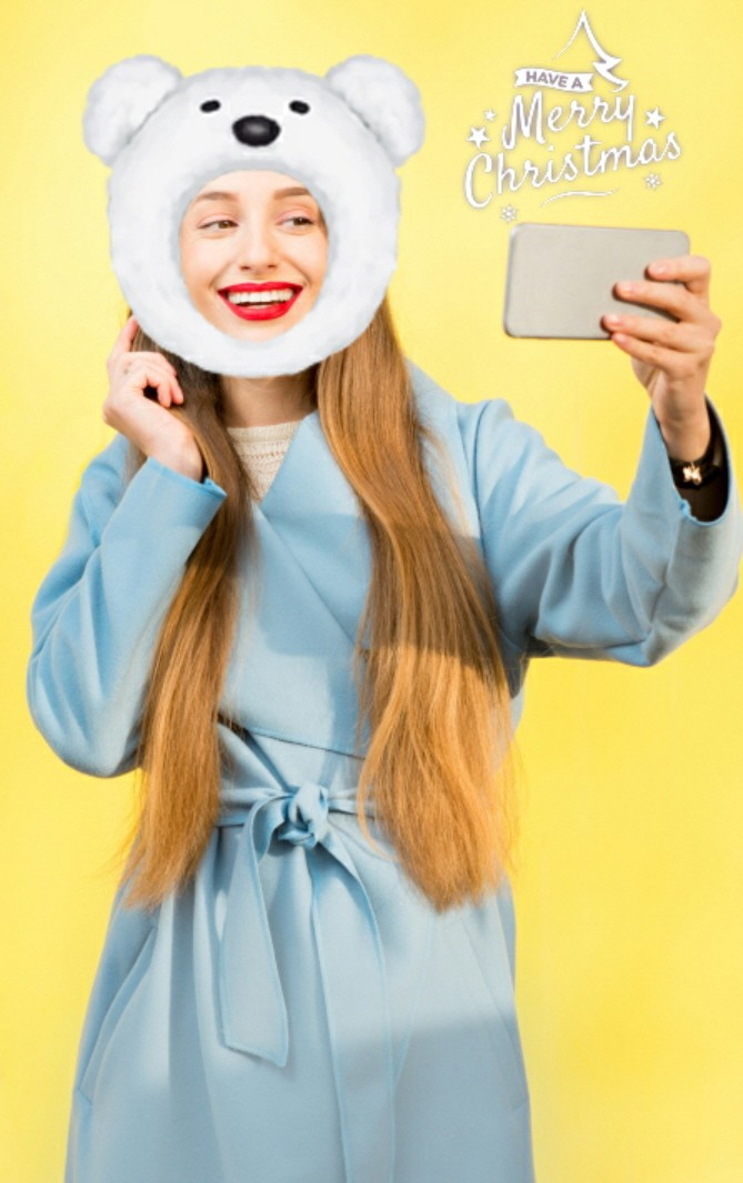 A woman takes a selfie as her face is decorated by a polar bear AR sticker.