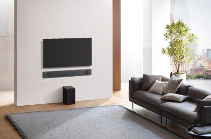An upper view of the LG Soundbar model SL9YG installed on the wall below an LG TV, with the LG Wireless Rear Speaker Kit model SPK 8 on the floor below