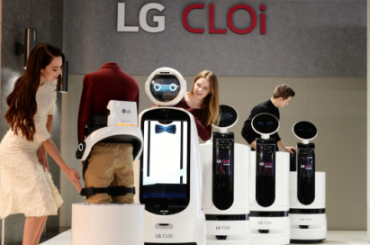 Female and male models look around the LG's CLOi commercial robot samples.