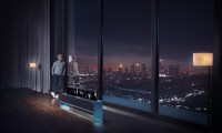 A man looking out the window at the city skyline at night, an LG SIGNATURE OLED TV R is reflecting a picture of the skyline