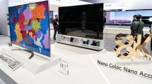 Two LG 8K NanoCell LCD TV models that are positioned the front and the back next to a rotating 8K promotional sign board