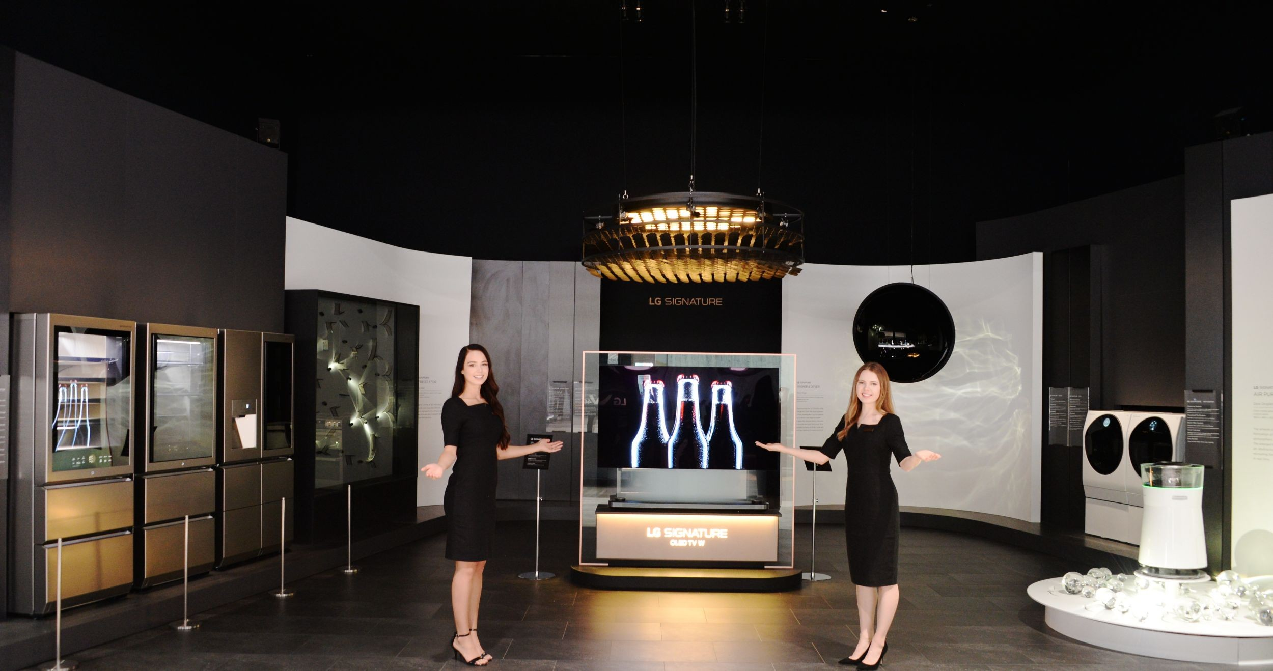 Two female models open their arms up to invite people to the LG SIGNATURE brand zone.
