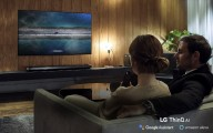 A couple using the LG ThinQ AI TV while sitting on their living room sofa