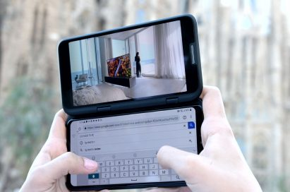A person holding the LG V50 ThinQ 5G and LG Dual Screen, with the Dual Screen showing a video while the main screen is being used for a Google search