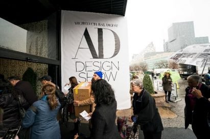 A group of visitors pass by a big logo banner for the 2019 Architectural Digest Design Show in New York City.