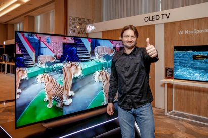 The world's youngest ever chess grandmaster Sergey Karyakin stands in front of LG's OLED TV, giving a thumb up towards the camera.