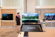 A female model posing in front of LG OLED TV with other LG TV products in behind.