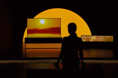 LG SIGNATURE OLED TV R model 65R9 displayed in the dark for the Redefining Space installation, with a model standing in front at Milan Design Week.