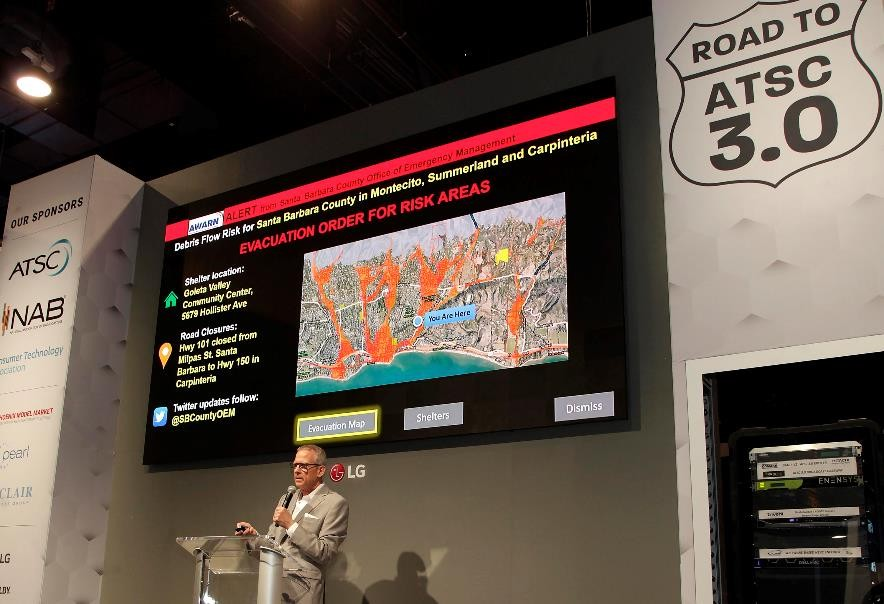 LG's large display hangs against the wall over the podium for a presentation session during the Road to ATSC 3.0 exhibit event.