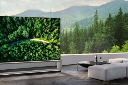 LG 8K OLED TV showing a road in the woods is placed in a spacious room with a spectacular view