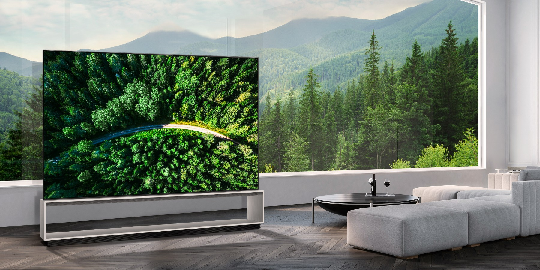 LG 8K OLED TV showing a road in the woods is placed in a spacious room with a spectacular view.